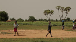 Niger, Africa. July 2013. Extreme long shot of kids walking at a traditional vil Footage