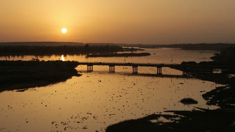 Extreme wide shot of an african golden sunset by the Niger river with bridge and Footage