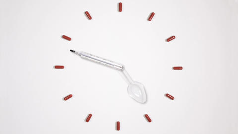 Clock of twelve pills, medical thermometer and plastic spoon Footage