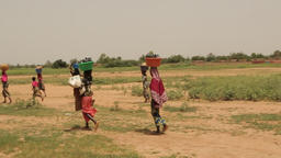 Niger, Africa. July 2013. African women carrying goods on their heads Footage