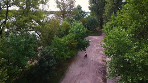 Forward reveal aerial view from mother running with strollers Live Action