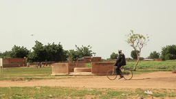 Niger, Africa. July 2013.Wide shot of african riding a bicycle near a water well Footage