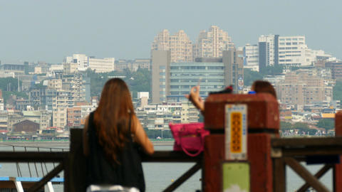 Two girls making pictures in front of skyline Tamsui Footage