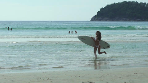 Young Woman Carrying A Surfboard Across The Beach Footage