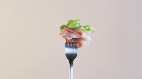Rotating Fork With Ham and Lettuce on Almond Background Live Action