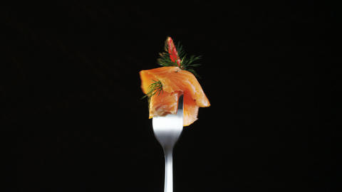 Rotating Fork With Salmon and Chili Pepper on Black Background Live Action