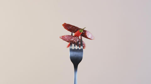 Rotating Fork With Two Sausages and Chili Pepper on Almond Background Footage