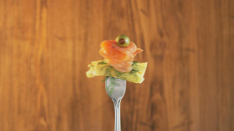 Rotating Fork With Salmon and Cheese on Wooden Background Footage