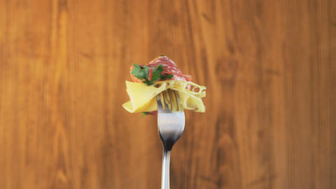 Rotating Fork With Salami and Cheese on Wooden Background Footage