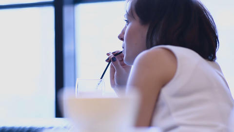 Beautiful woman drinks cacao in cafeteria Live Action