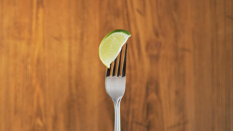 Fork With Lime on Wooden Background Footage