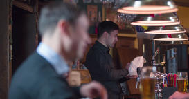 Speaking smiling man at beer pub bar counter close-up 4k video. Bartender Footage