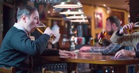Men pub guests drinks beer at bar counter 4k video. Male friends taste lager Footage