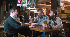 Men friends talks drinks beer at pub bar HD slow-motion video. Laughing smiling Footage