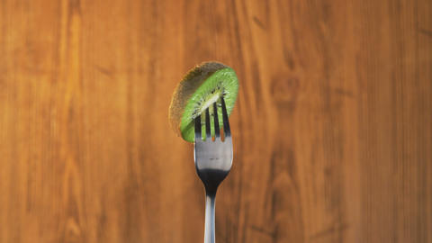 Fork With Kiwi on Wooden Background Footage