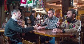 Friends talks drinks beer pub bar 4k video. Men taste lager from glasses Footage