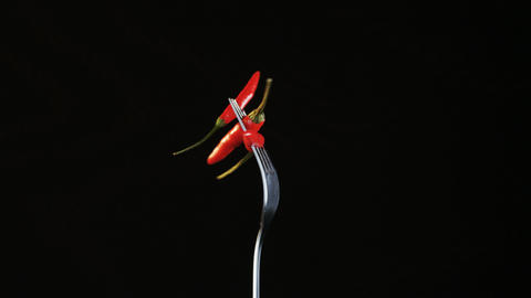 Fork With Three Chili Peppers on Black Background Stock Video Footage