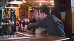 Men friends toast cheers beer drinks at pub bar counter HD slow-motion video Footage