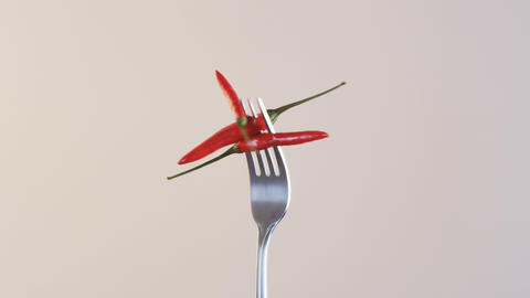 Fork With Three Chili Peppers on Almond Background Footage