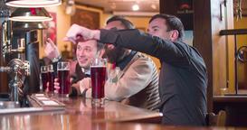 Friends talks drinks beer at pub bar 4k video. Men having fun looking discussing Footage