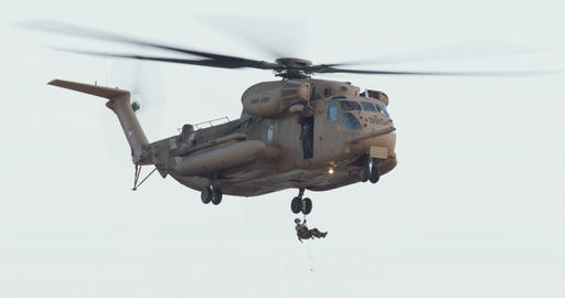 Sikorsky CH-53E Super Stallion hovering while a soldier is rescuing a wounded pe