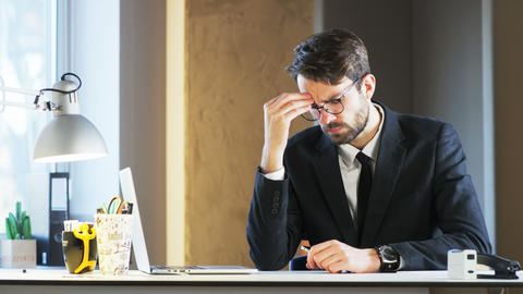 Young Businessman Having a Headache and Holding a Mobile Phone Footage
