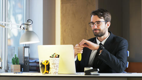 Young Businessman Eating Banana During Lunch Break Footage