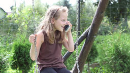 Young girl on a swing is receiving a call on her smartphone Footage
