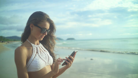 Woman Using Her Mobile Phone.On The Beach Filmmaterial