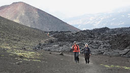 Female tourists walking on background of lava flow and cone of volcano Footage