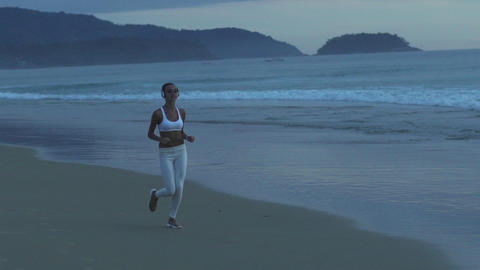 Fitness Woman Running At Dusk On A Tropical Beach Footage