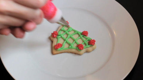 Adding Red Icing To Bell Shaped Christmas Cookie Footage