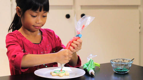 Asian Girl Adds Red Icing To Christmas Cookie Stock Video Footage