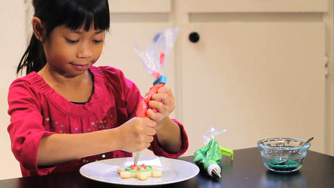 Asian Girl Adds Red Icing To Christmas Cookie stock footage