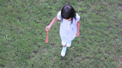 Asian   Girl   Spinning   Around   While   Making   Bubbles stock footage