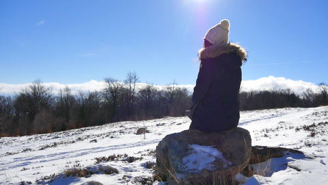 Girl sitting on mountain rock and enjoying beautiful winter view of clouds Footage