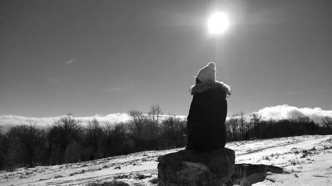 Alone girl sitting on the mountain stone enjoying beaufitul winter view, monochr Footage