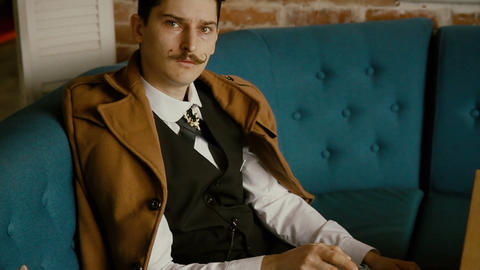 man with a mustache sitting on a sofa ビデオ