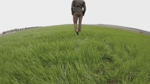 man in a leather jacket walking in field Footage