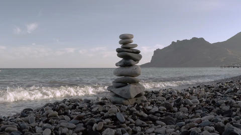 Stone pyramid on a seashore in background of sea and rocks Live Action