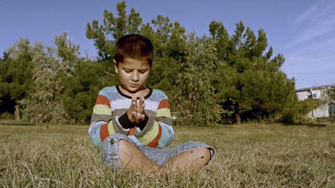 boy claps his hands while sitting on the grass Footage