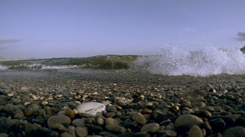 wave washes up to the shore and washes away the stones fly spray Footage