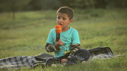 boy sitting in the park and sing Footage
