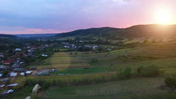 Aerial view of countryside village and crops, sunset Footage