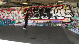 Boy on skateboard against graffiti wall London UK ビデオ