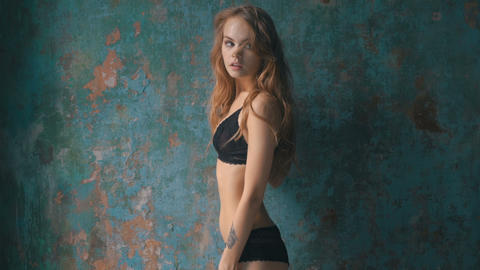 Beautiful slim girl in black lingerie posing near textured old wall Live Action