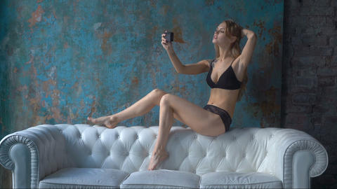 Sexy woman in underwear sitting on the sofa and taking selfie Footage