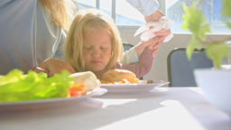 Little Blond Girl Eats Chicken Mother Cleans Hand at Table Footage