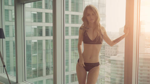 Beautiful girl in lingerie posing near the window on the background of the city Footage