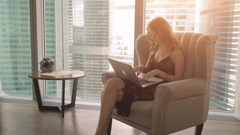 Pretty lady working on her laptop while sitting in an armchair at home Footage